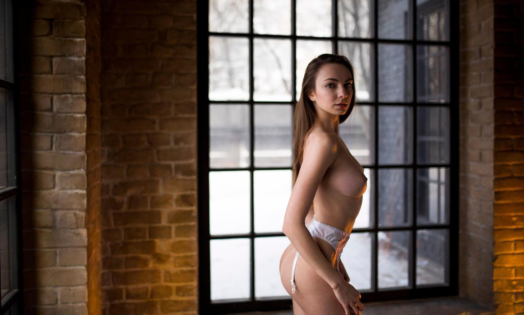 Фото Девушка у окна, голая грудь, белые подвязки для чулков на поясе, скачать картинку бесплатно