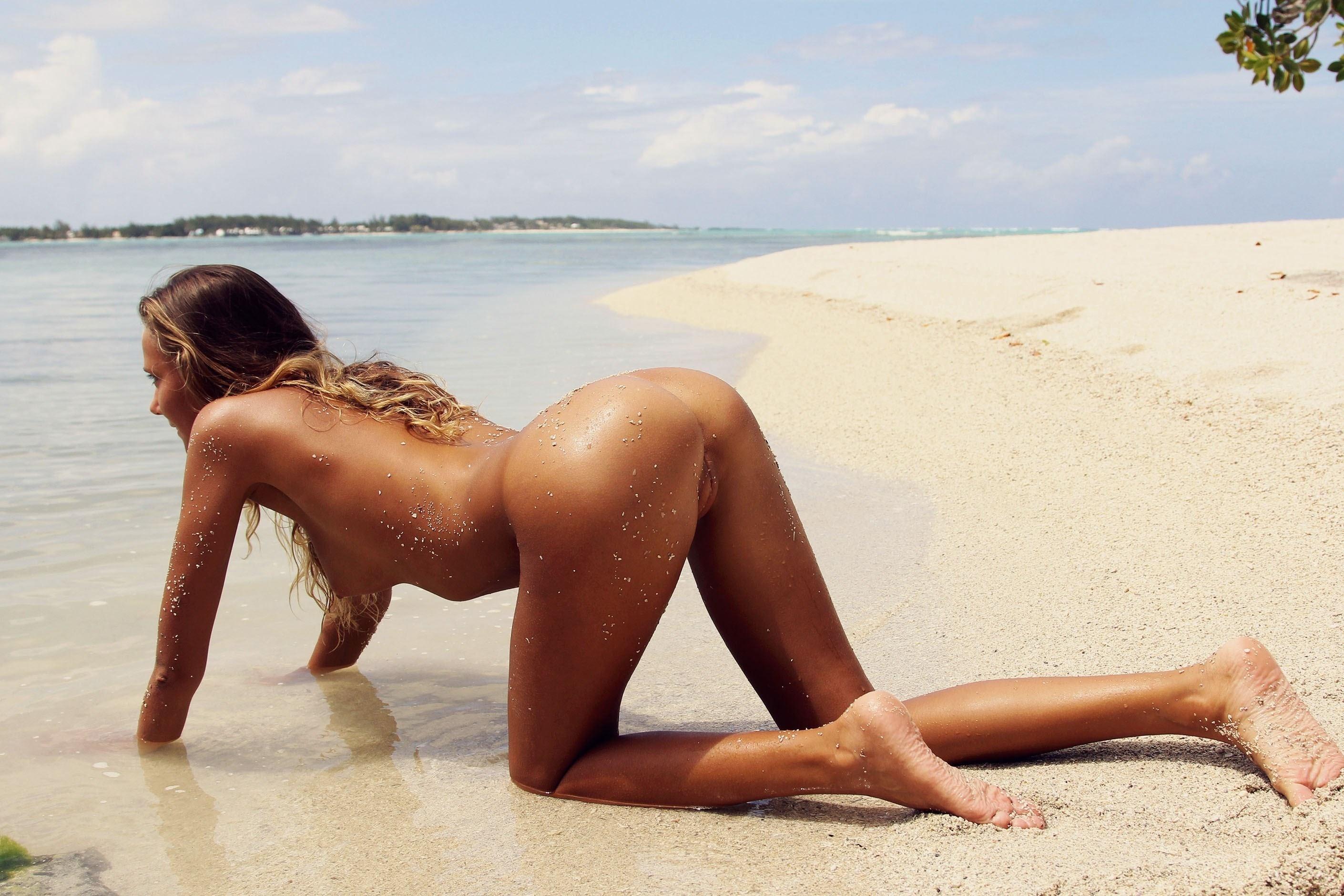Фото Голая загорелая девушка ползет на четвереньках по песку вдоль берега, скачать картинку бесплатно
