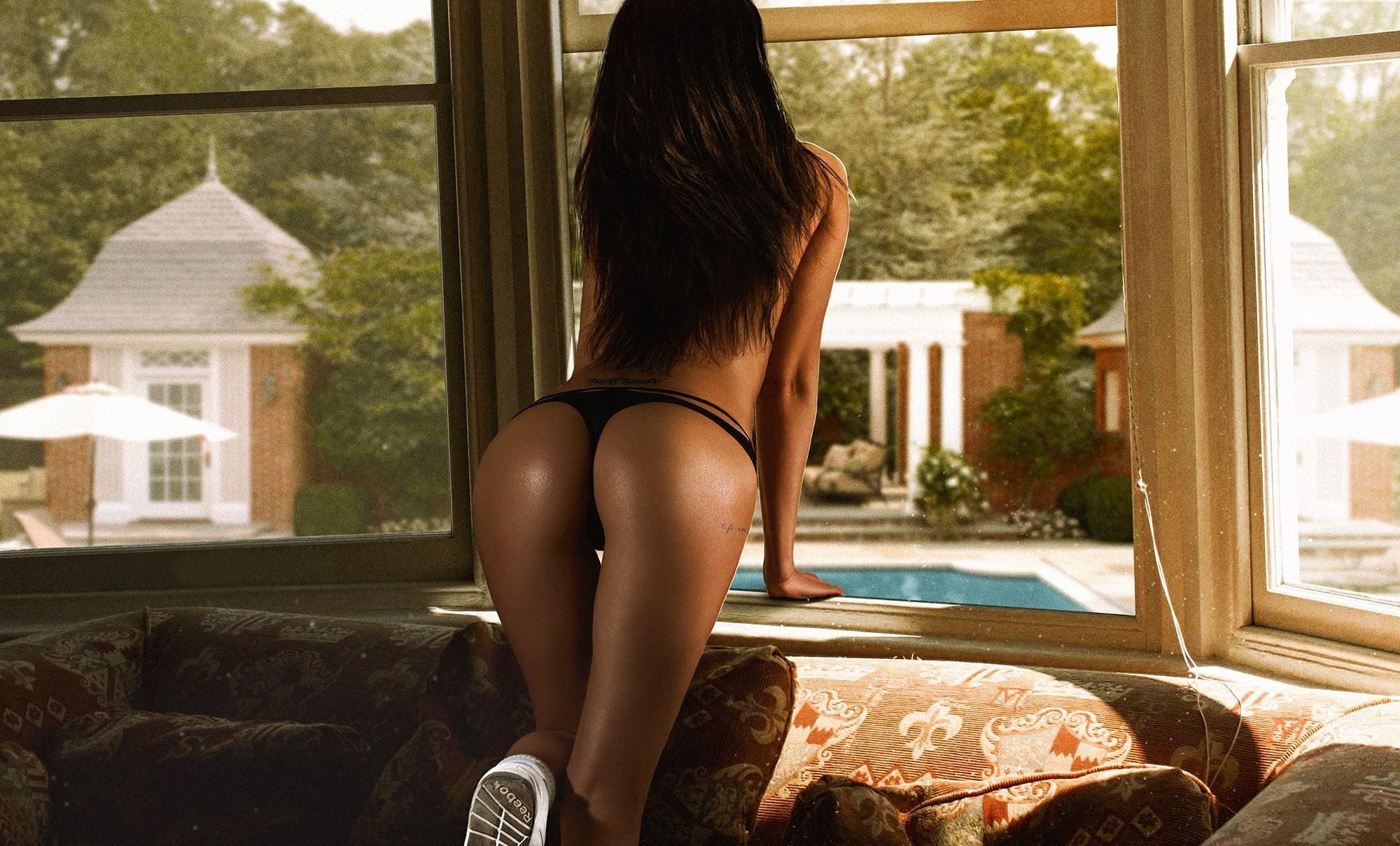Фото Влажная упругая попка в черных стрингах, сексуальная брюнетка смотрит в окно, скачать картинку бесплатно