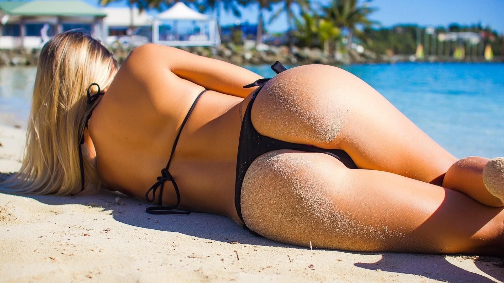 Фото Девушка загорает на песке, море, попка, песочек на попе, черные трусики, купальник, жара, скачать картинку бесплатно