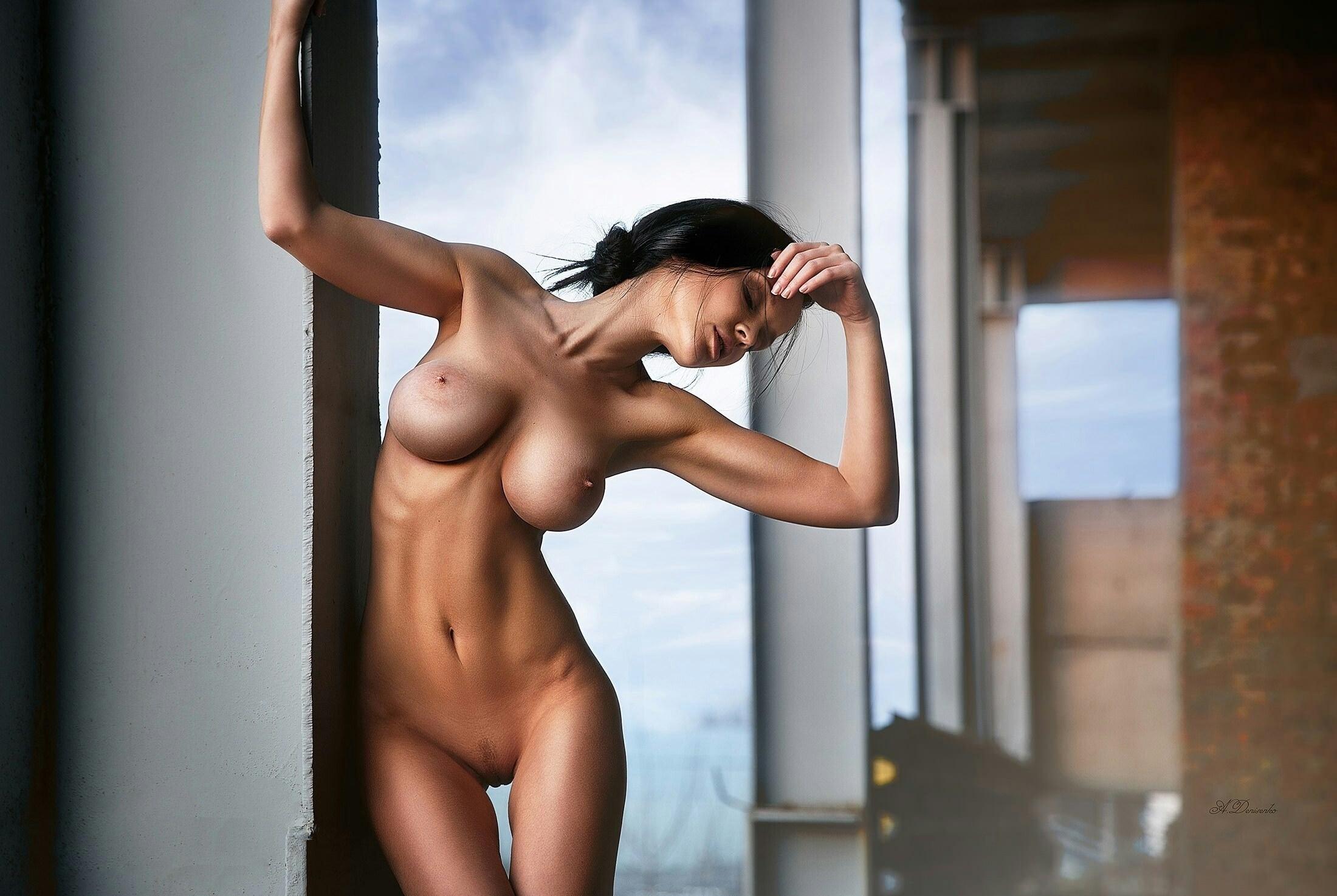 Фото Голая соблазнительная брюнетка позирует, стоя у окна, прекрасное тело, сиськи, плоский животик, скачать картинку бесплатно