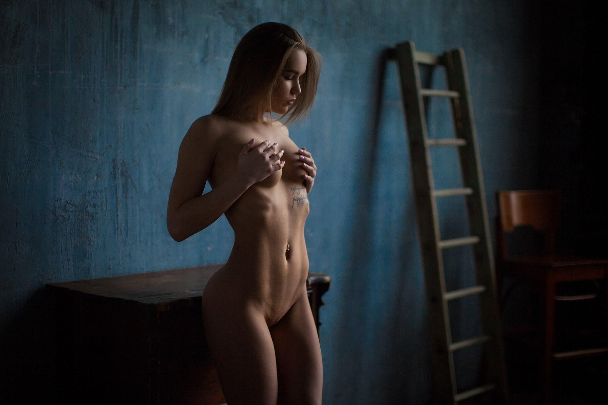 Фото Голая девушка прижалась попой к тумбе, сжимает грудь, сексуальное тело, пупок, животик, бедра, секси, лестница, скачать картинку бесплатно