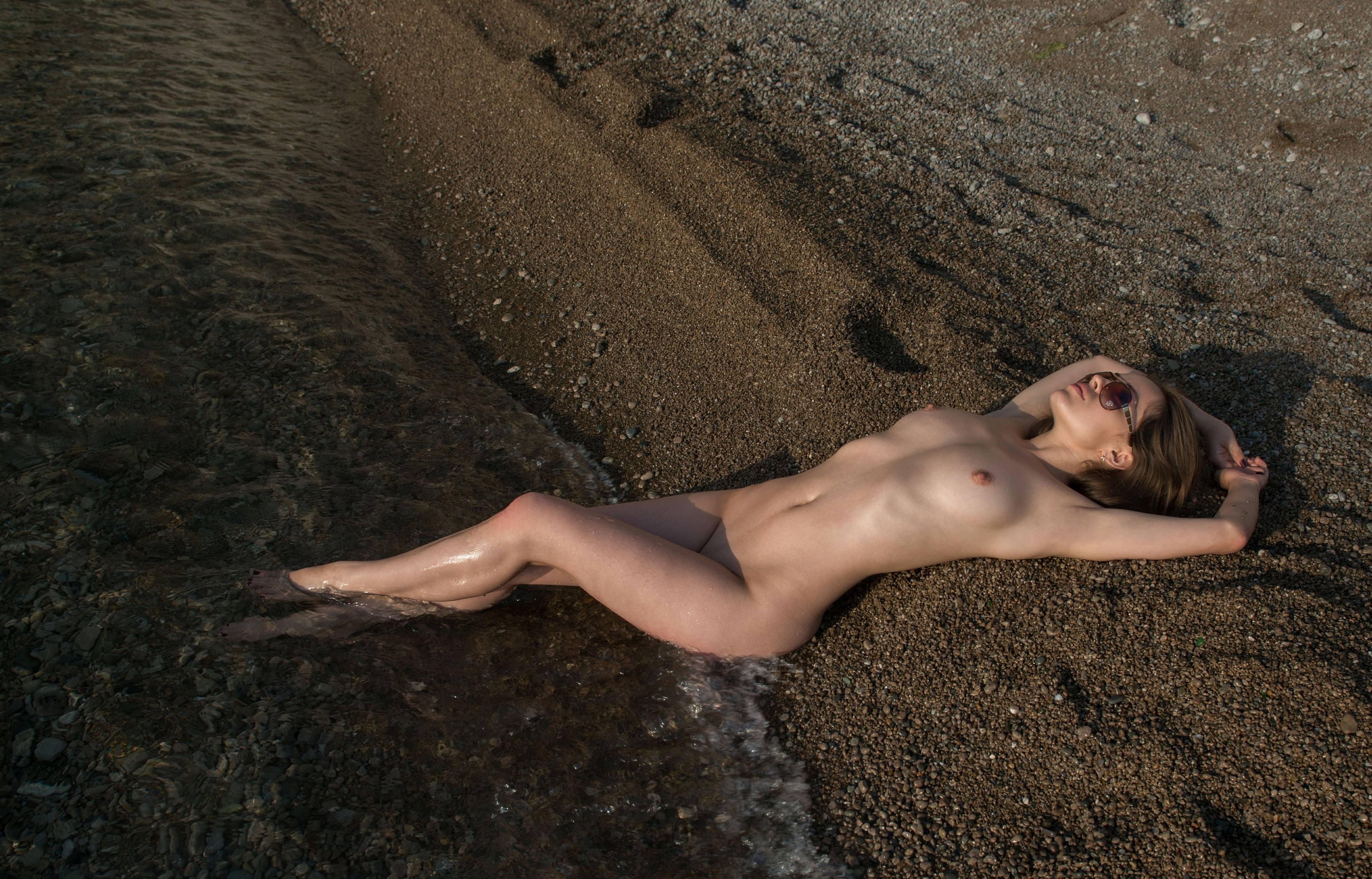 Фото Голая девушка на песке, ножки в воде, мокрая сучка на море без одежды, скачать картинку бесплатно