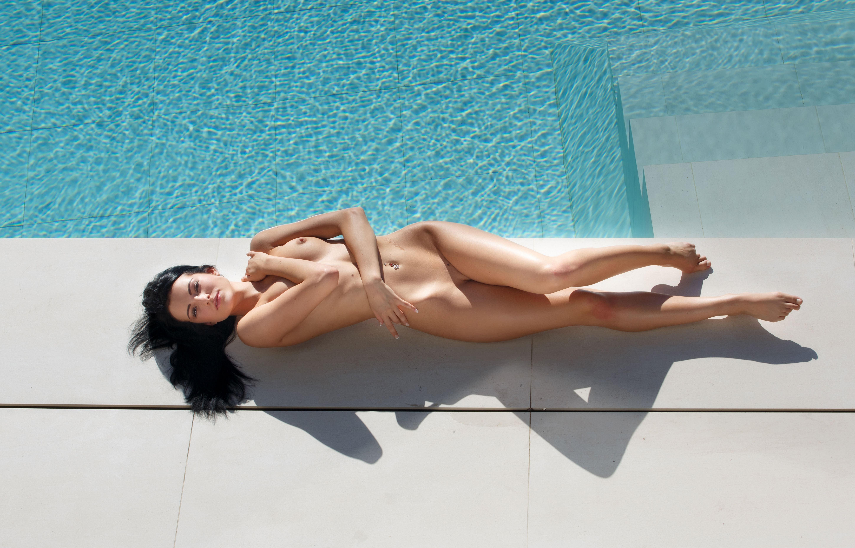 Фото Голая брюнетка лежит на краю бассейна, слегка прикрыв грудь, скачать картинку бесплатно
