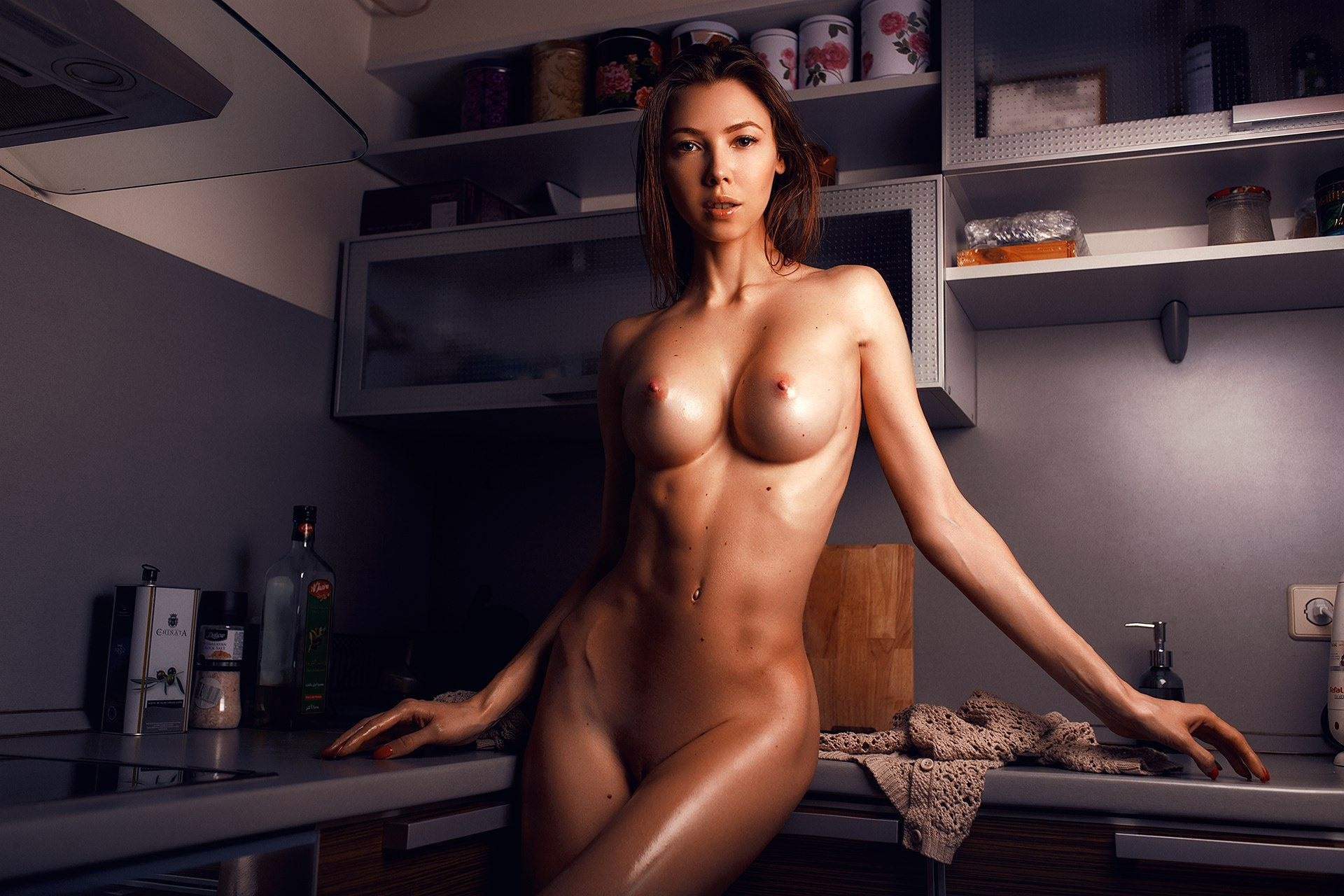 Фото Обнаженная девушка с шикарной фигурой позирует на кухне, упругая грудь, блестящее тело, скачать картинку бесплатно