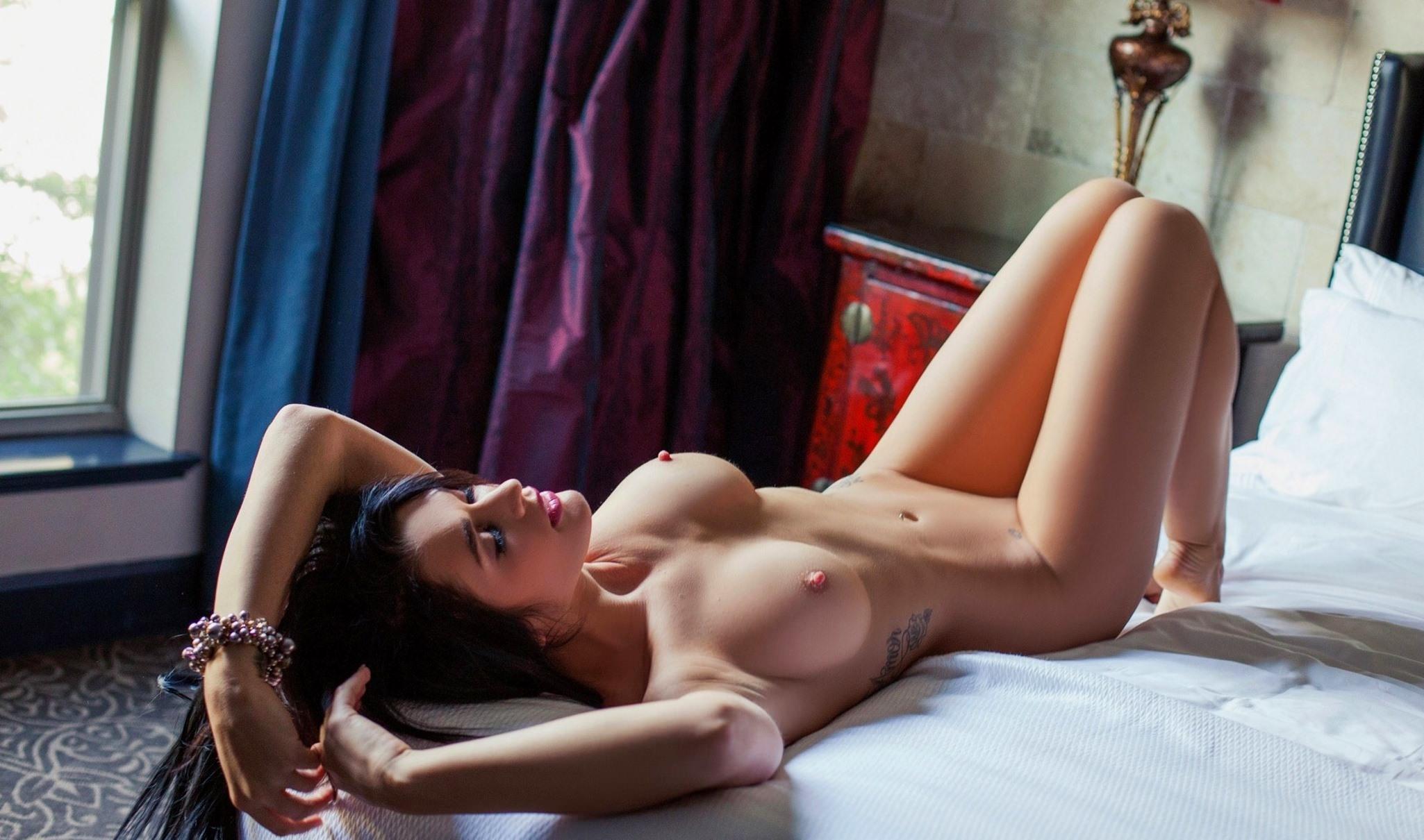 Фото Обнаженная брюнетка в спальне, упругие соски, красивые сиськи, браслет, тату на боку, скачать картинку бесплатно