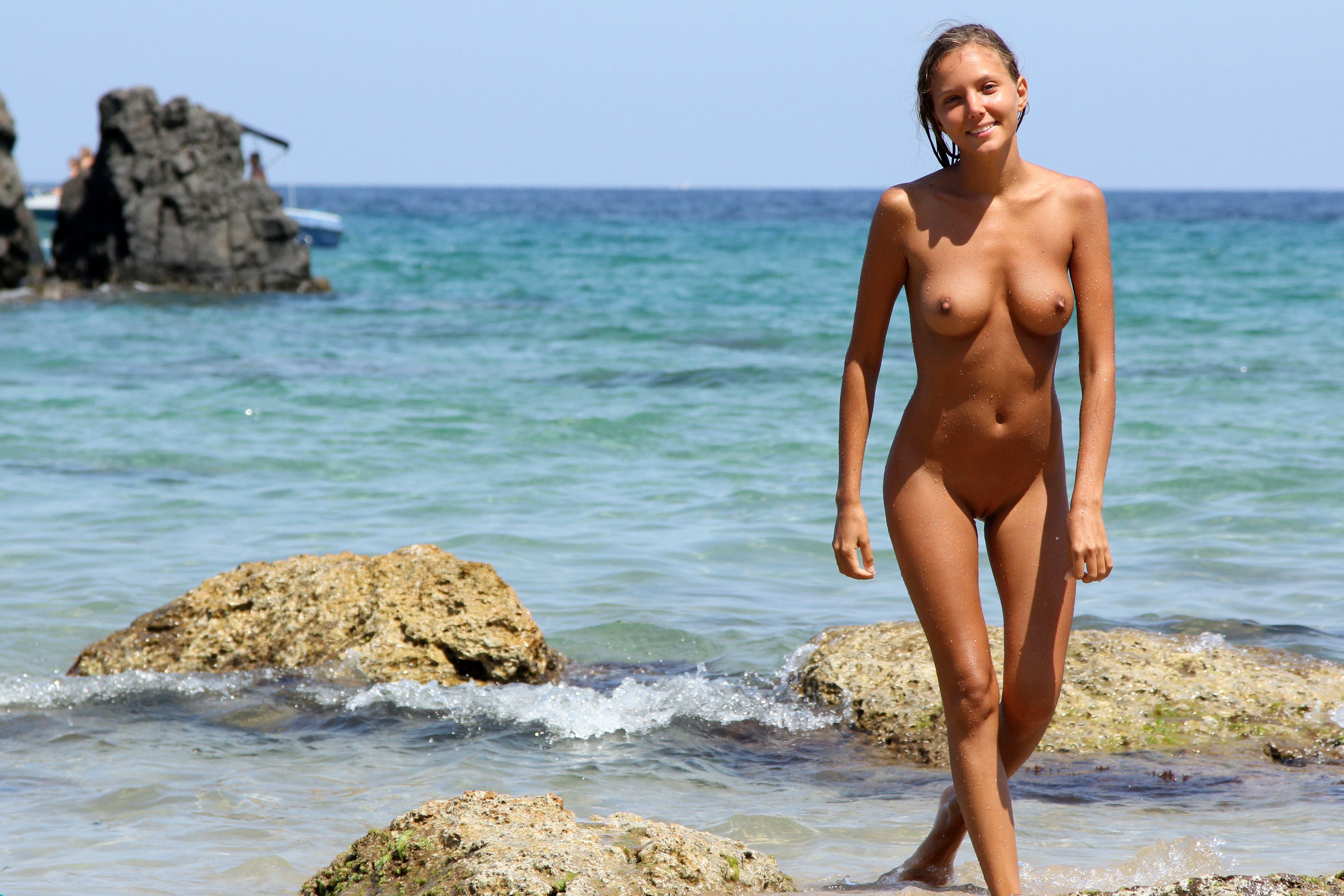 Фото Загорелая голая девушка гуляет вдоль моря, улыбка, сексуальное тело, скачать картинку бесплатно
