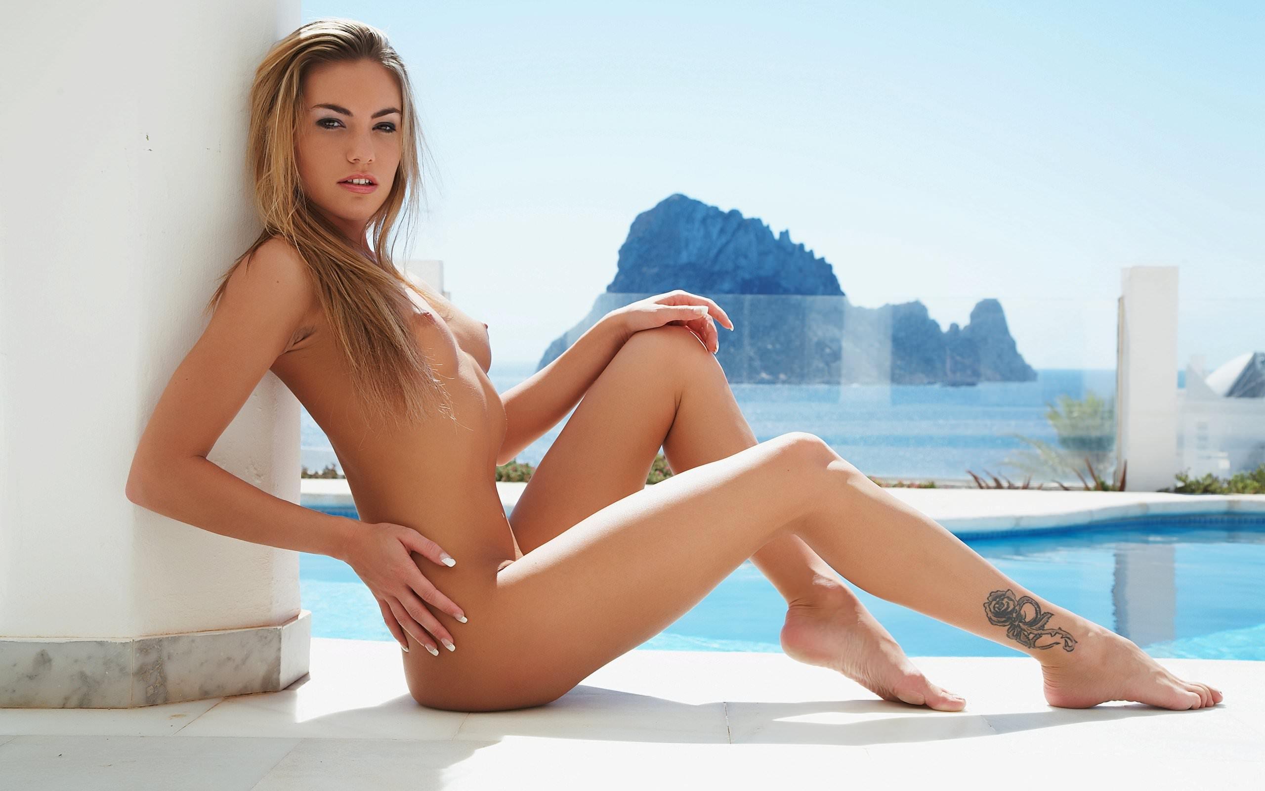 Фото Летняя эротика, голая девушка с тату на ноге, маленькая грудь, длинные ножки, бассейн. Naked girl, poolside, tattoo on the leg, sexy legs, sunlight, blue sky, summer erotic, скачать картинку бесплатно