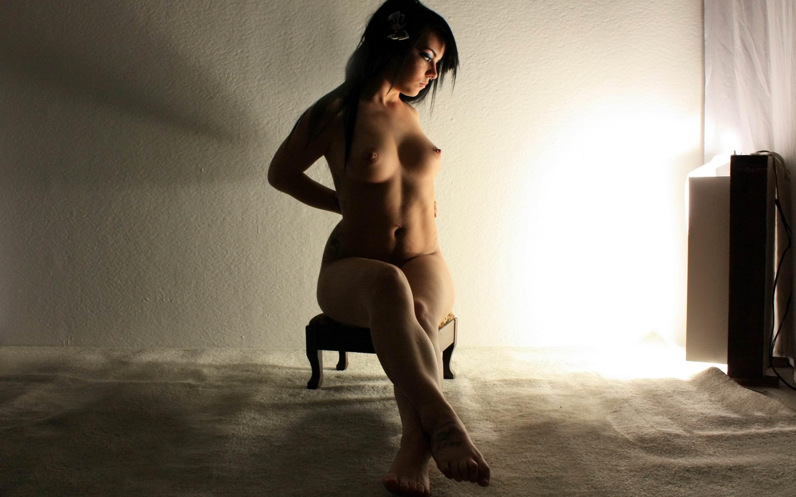 Фото Сексуальная обнаженная девушка мило сидит на низкой табуретке, убрав руки за спину, выставила ножки вперед, томный свет, вечер, брюнетка, острые соски, упругие натуральные сиськи. Naked girl on the chair, light in the room, hands behind, tits, nipples, brunette, скачать картинку бесплатно