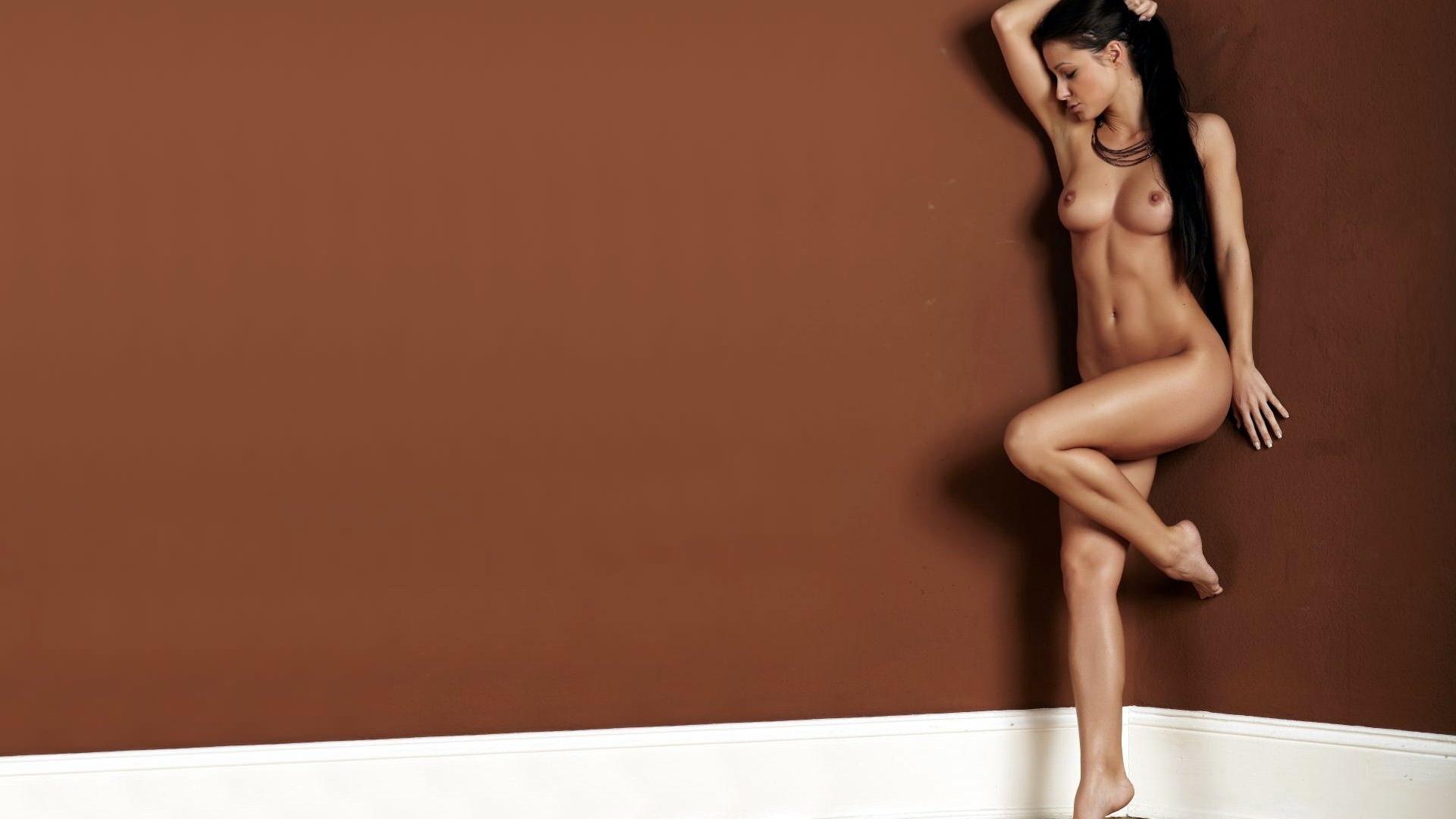 Фото Длинноногая голая брюнетка на коричневом фоне, согнула левую ногу. Naked girl, brown wall, sexy body, long black hair, brunette, sexy legs, leg up, posing, hot, скачать картинку бесплатно