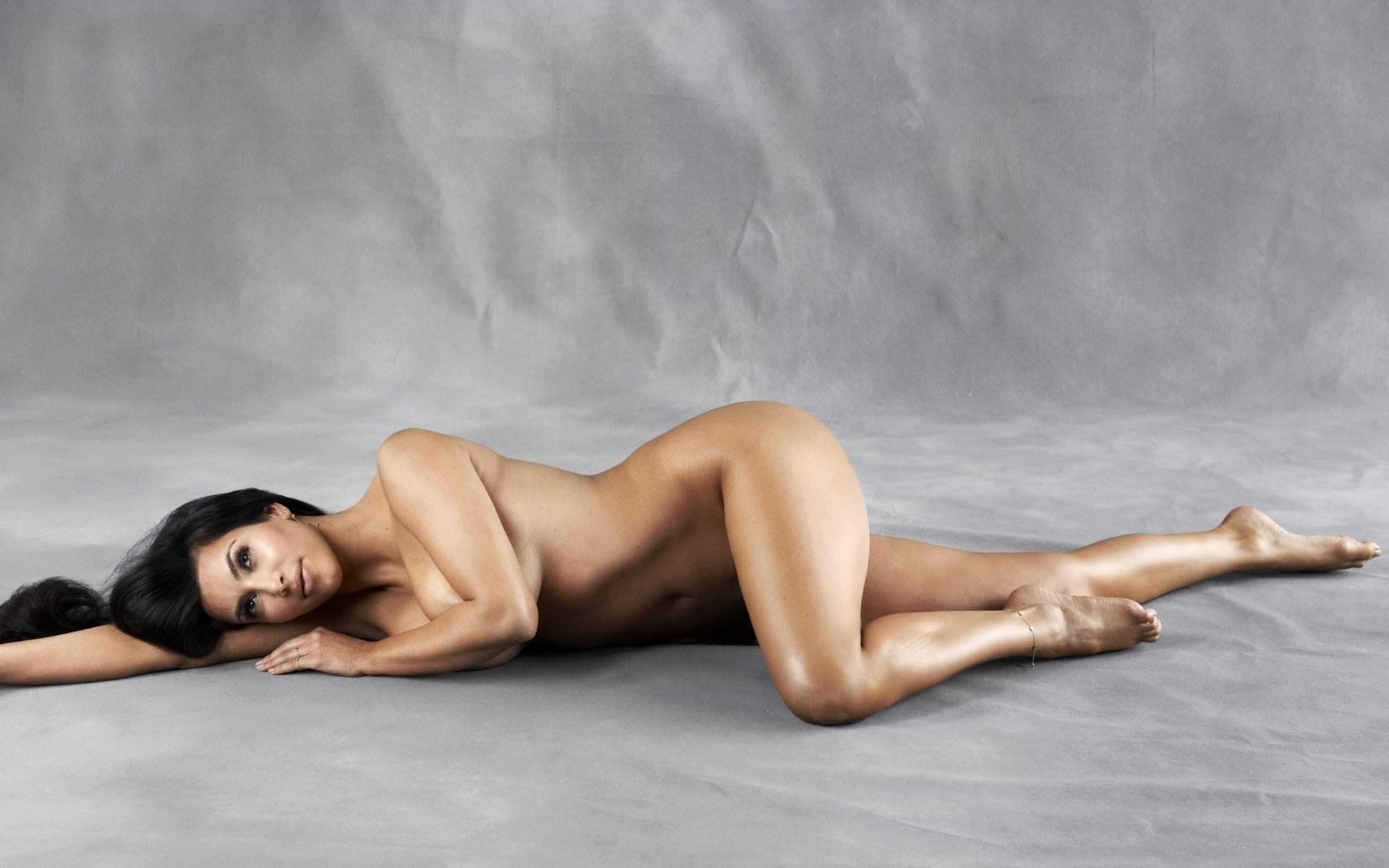 Фото Голая девушка с блестящим сексуальным телом лежит на полу, серый фон, дым, обнаженная брюнетка. Naked brunette on the floor, legs shine, gray, скачать картинку бесплатно