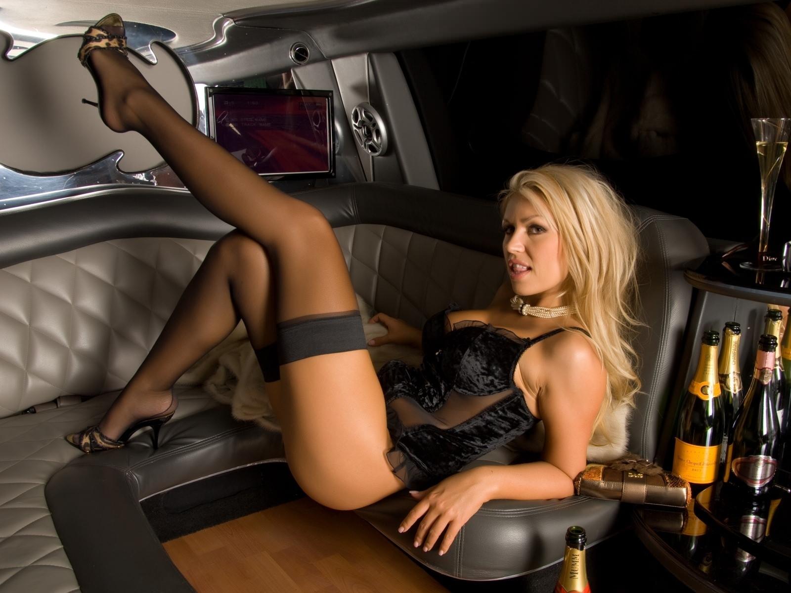 Фото Сексуальная блондинка в роскошном автомобиле с выпивкой и круглым диваном, ножки в чулках, черная ночнушка, соблазн, шампанское. Sexual blonde in the car, sexy legs in black stockings, sexy thighs, black corset, sexy body, alcohol, posing, скачать картинку бесплатно