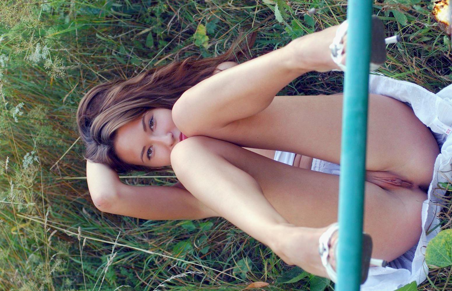 Фото Раскрепощенная девушка без трусиков под белой юбкой легла на зеленую траву, ножки на перилах, красивая голая киска между ног, девушка показала, что у нее под юбочкой. Beauty, no panties, sexy girl on the green grass, white skirt, genttle legs, sweet pussy, labia, скачать картинку бесплатно