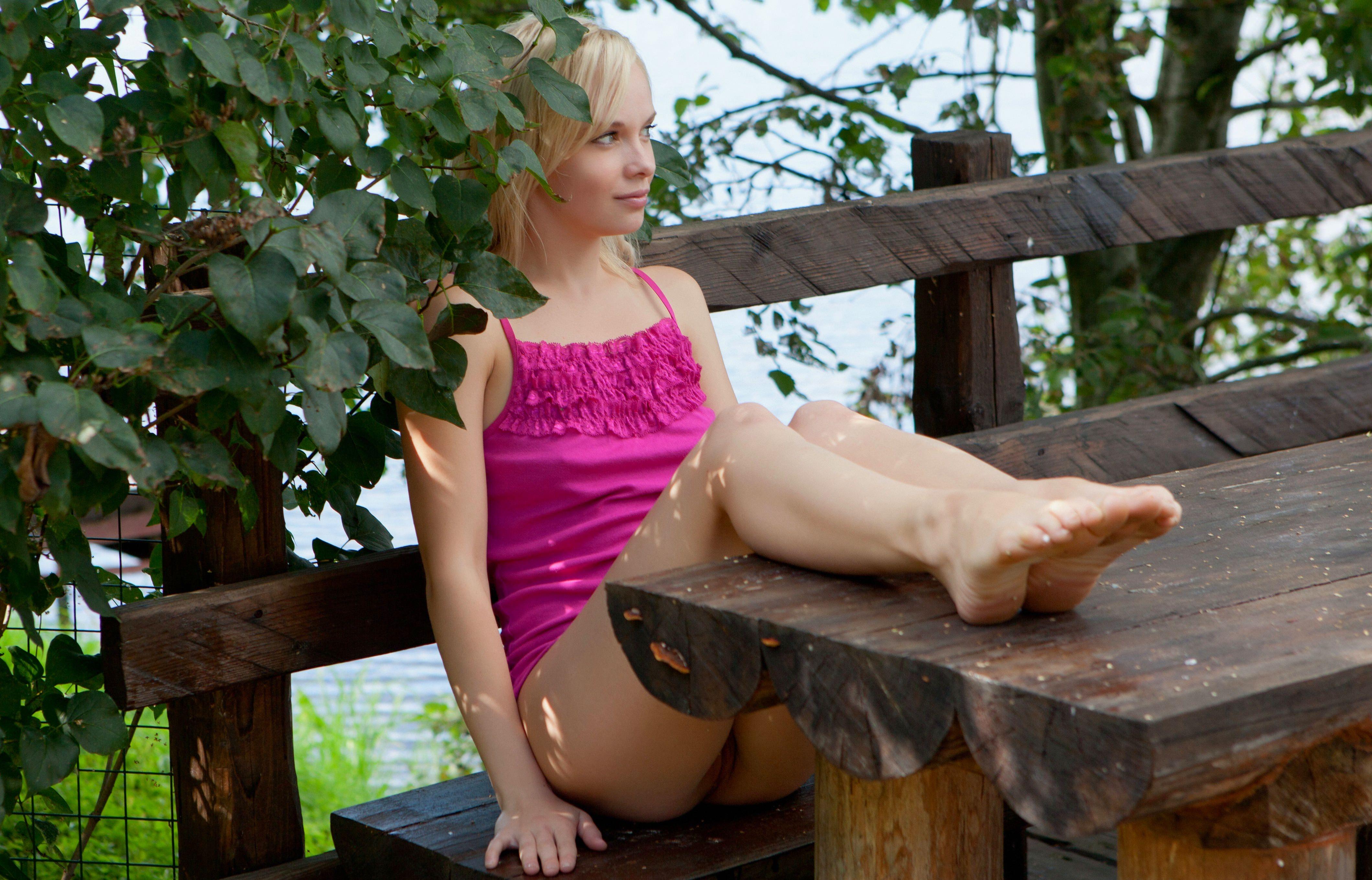Фото Раскрепощенная молодая блондинка в розовой майке, девушка положила ноги на стол, на надела трусики, девушка на природе. Young girl put feet on a table, legs, garden, wood bench, pink undershirt, no panties, green leaves, скачать картинку бесплатно