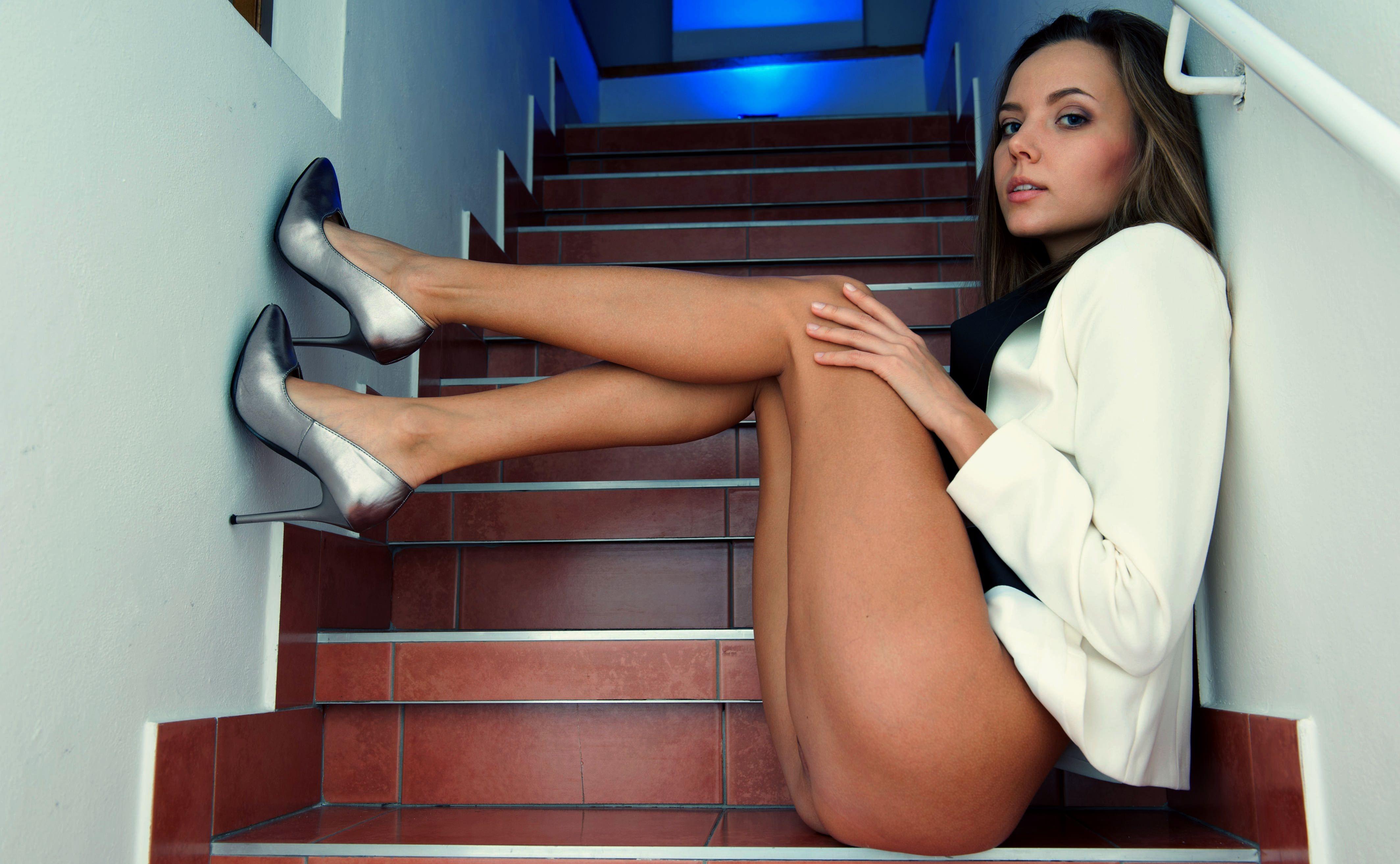 Фото Красавица без трусиков на лестнице в доме, красивая сексуальная девушка в белом пиджаке мило сидит на ступенях, красивые нежные ножки, загорелые сексуальные ножки, прекрасные бедра, серебристые туфли. Beautiful girl on the ladder, sexy naked legs, white blazer, jacket, tanned legs, silver high heels, beauty, скачать картинку бесплатно