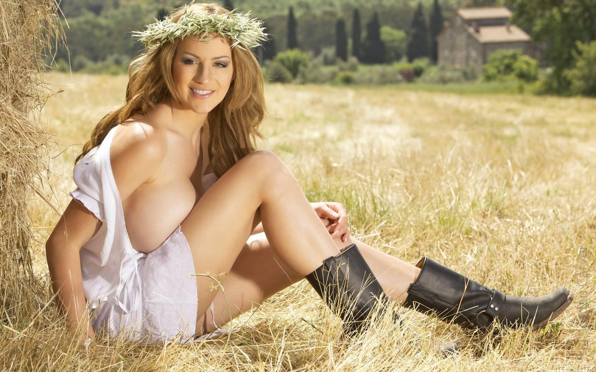 Фото Сисястая молодая девушка на сеновале, черные сапоги, белое деревенское платье, большая грудь, сиськи больше колена, венок на голове и милая улыбка, пышные волосы, девушка на траве. Country girl with big boobs, huge tits, grass, hay, wreath, black boots, smile, voluminous hair, скачать картинку бесплатно