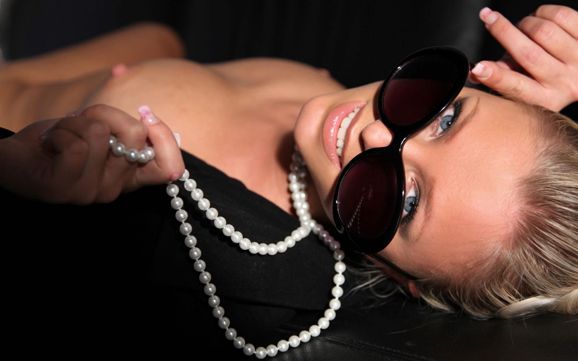 Фото Светская львица, голубоглазая красотка в темных очках, розовые сладкие губы, белоснежная улыбка, белые бусы, обнаженная маленькая грудь, набухшие упругие розовые соски. Black glasses, naked tits, pink nipples, sweet lips, smile, look, white beads, black blazer, glamourous girl, скачать картинку бесплатно