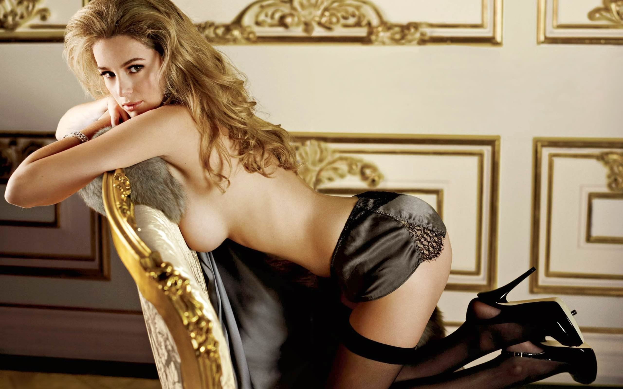 Фото Сексапильная девушка в черной кожаной юбке и чулочках, каблуки, обнаженной грудью прижалась к позолоченному креслу в гостиной. Sexy babe, latex skirt, black stockings, naked tits, gold chair, no bra, posing, sexy, voluminous hair, скачать картинку бесплатно