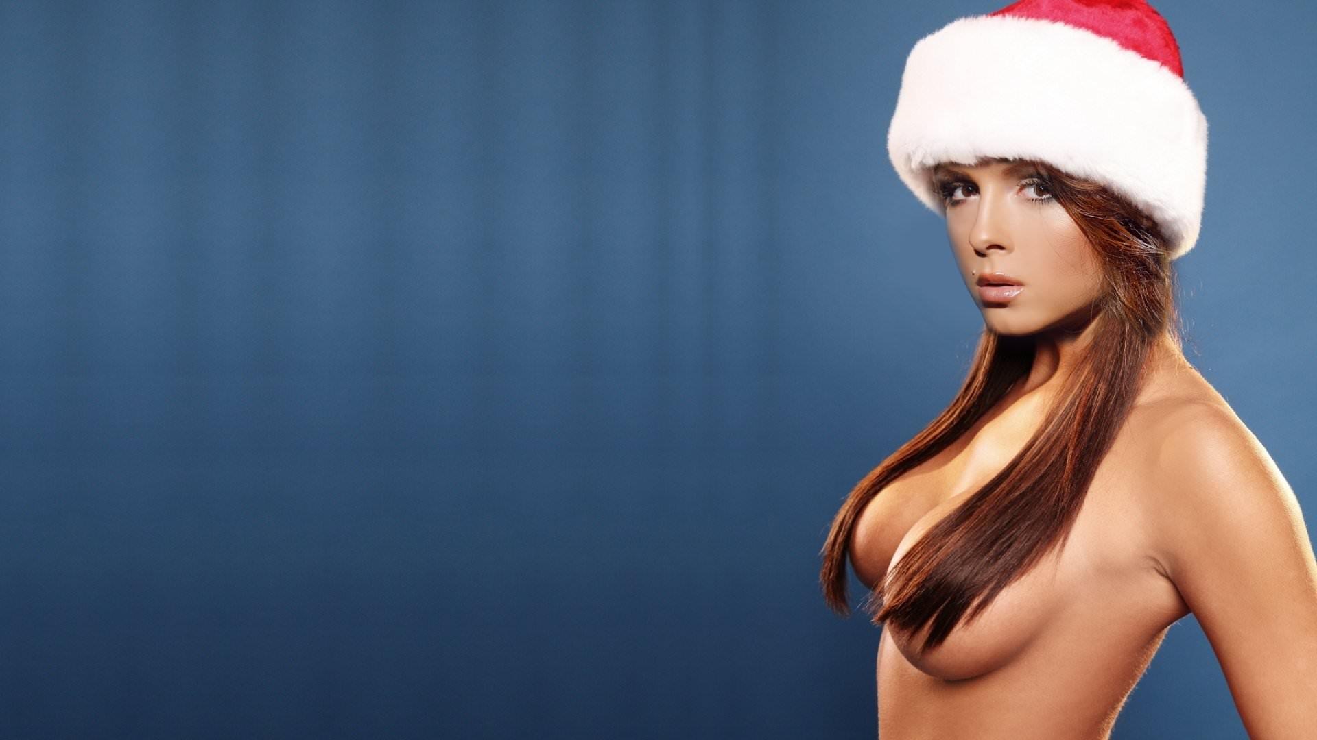 Фото Сексуальная Нюша в новогодней красной шапке, волосы на голых сиськах. Sexy young girl in a New Year's cap, hair on tits, sexy, dark blue background, скачать картинку бесплатно