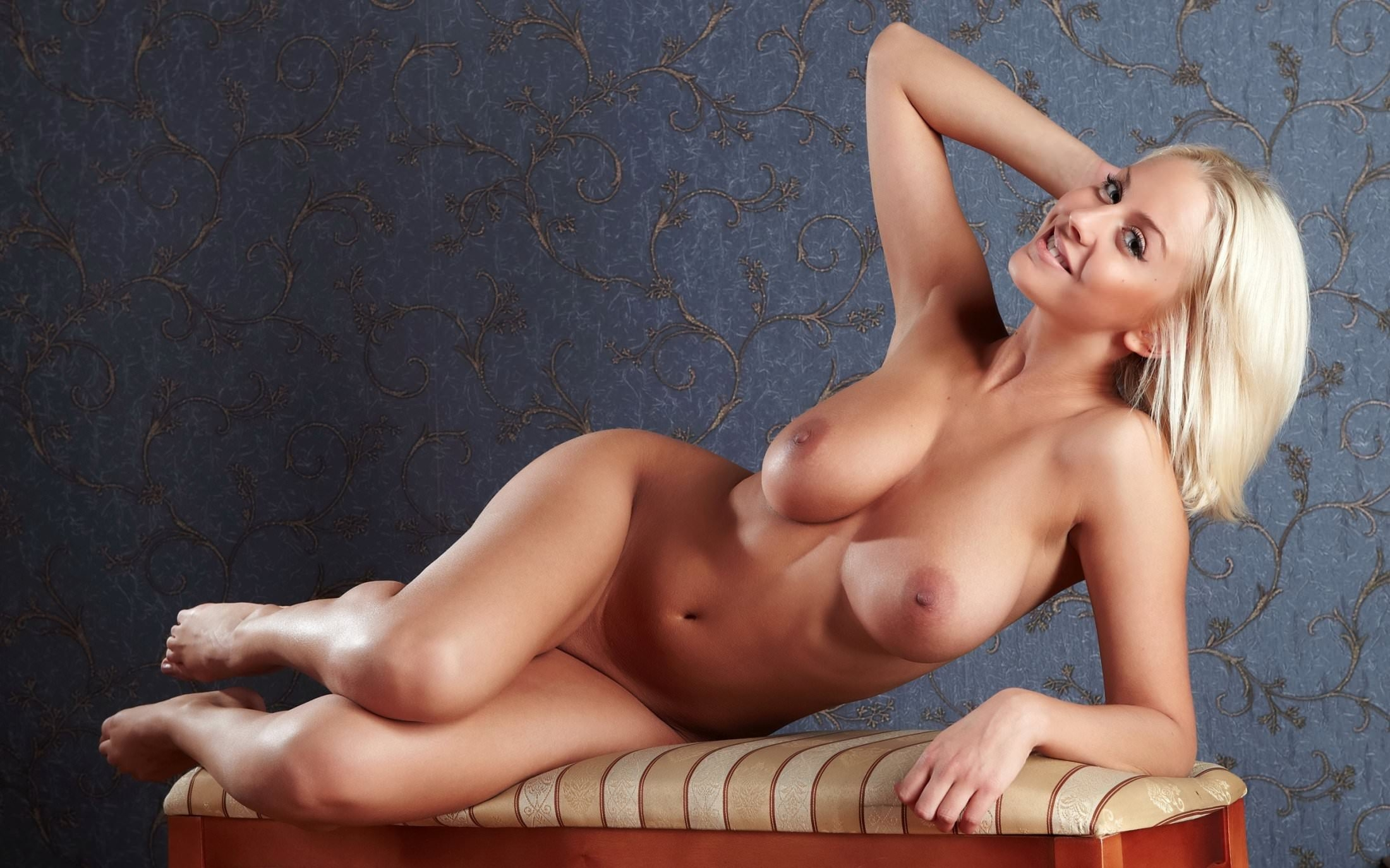 Фото Веселая блондинка разделась до гола и прилегла на пуфик, голые сиськи, блестящее сексуальное тело. Naked blonde, cool tits, sexy body, posing, padded stool, legs, nipples, скачать картинку бесплатно