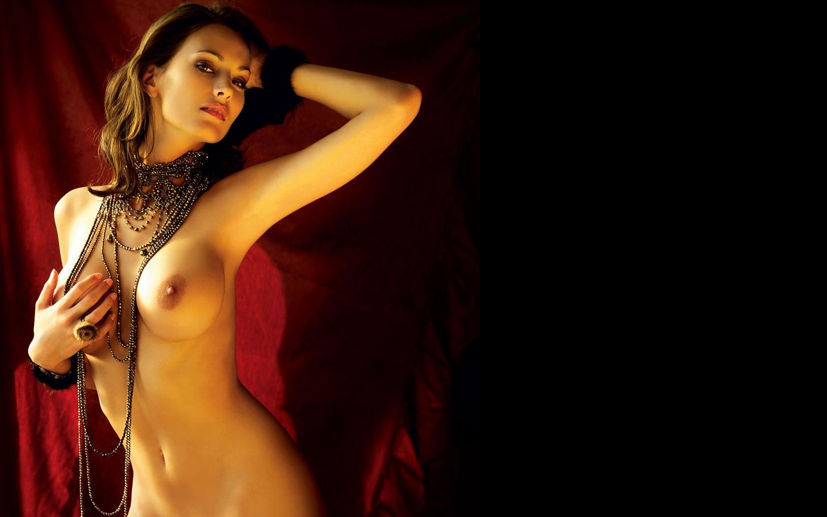 Фото Соблазнительная голая девушка с черными бусами на шее, красивые голые сиськи, прикрыла одну сиську рукой, соблазн в темноте. Naked girl, nice tits, round tits, nipple, black and red background, beads, sexy, скачать картинку бесплатно