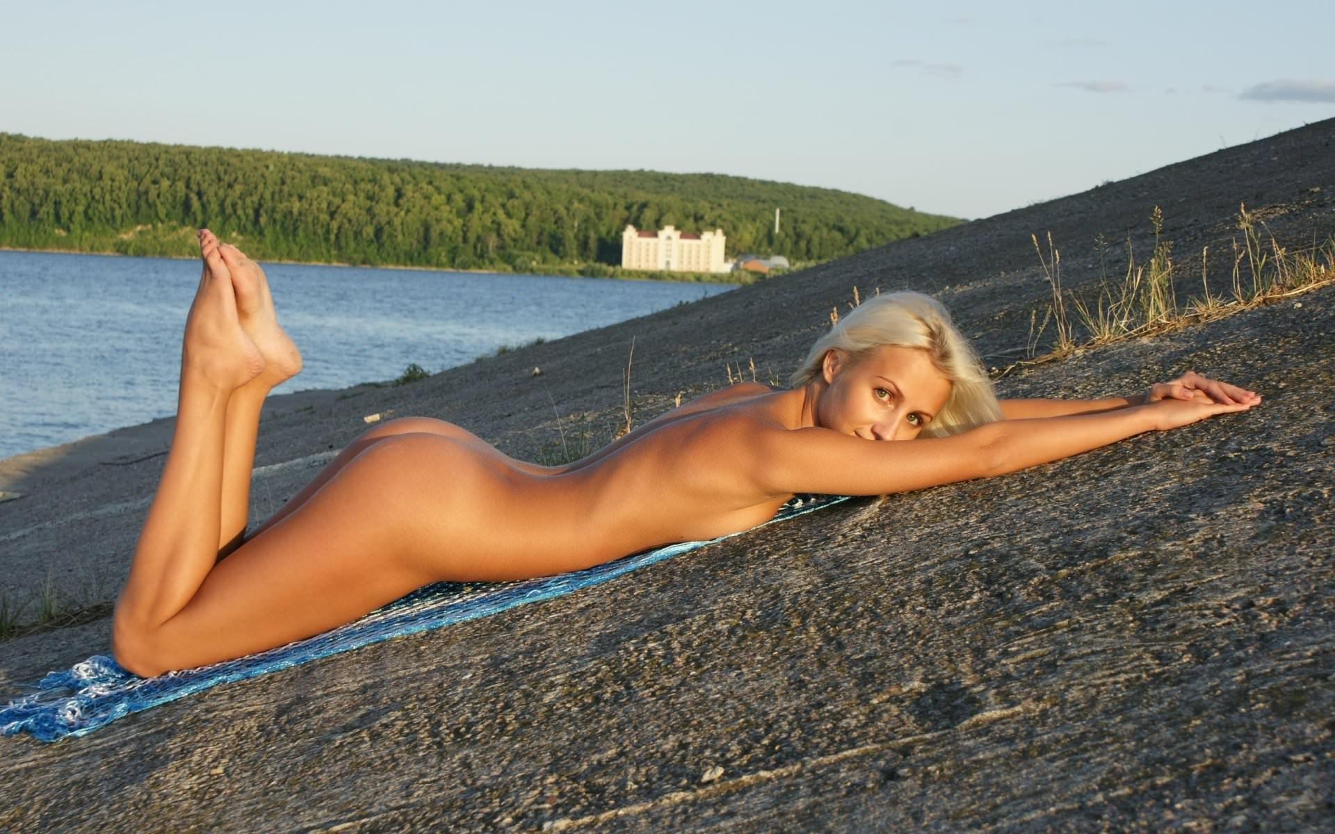 Фото Обнаженная сексуальная блондинка мило лежит у озера на склоне на животике, загорелое сексуальное тело. Naked blonde, outdoors, sexy, tanned body, perfect body, lake, скачать картинку бесплатно