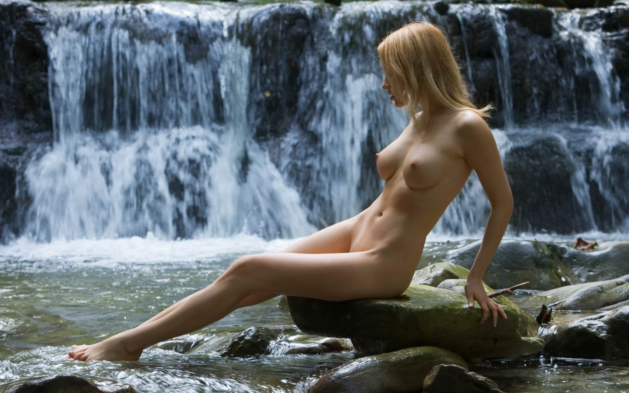Milla in splashing around naked in a waterfall