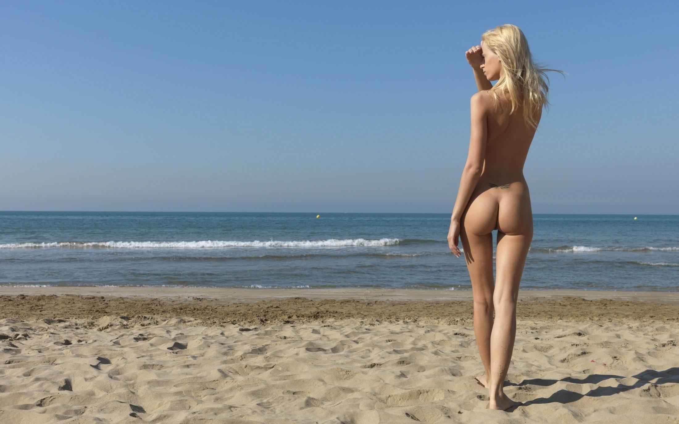 Фото Голая стройная блондинка смотрит на горизонт вдаль, закрыв ладонью глаза от солнечного света, стройные ножки, красивая упругая попка, пляж, море, синее небо, песок, нудистка. Skinny blonde on a beach, sand, nude girl, nice ass, harmonous legs, sea, horizon, скачать картинку бесплатно