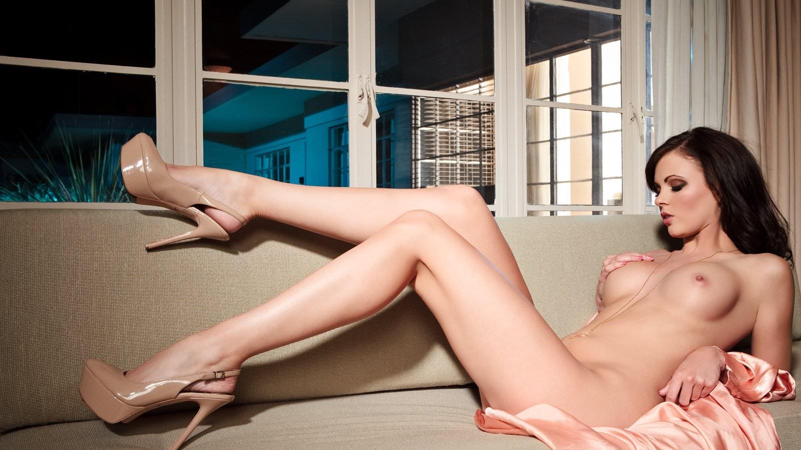 Фото Длинноногая соблазнительная девушка ласкает грудь, упругие сиськи, длинные красивые ножки, бежевые туфли, диван. Long sexy legs, high heels, naked brunette, pink silk dressing gown, cool tits, sofa, sexy body, скачать картинку бесплатно